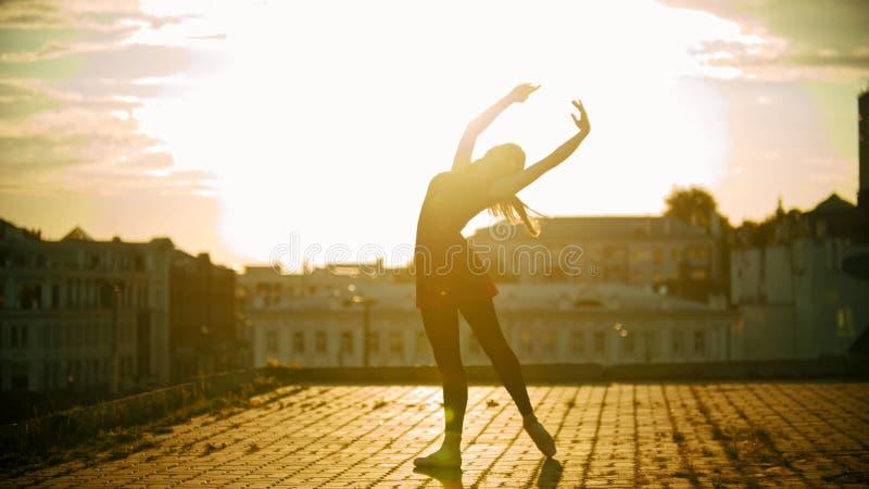 Une silhouette de ballerine de jeune femme dans la position de robe dans la pose gracieuse sur le toit sur un fond de moderne photo stock
