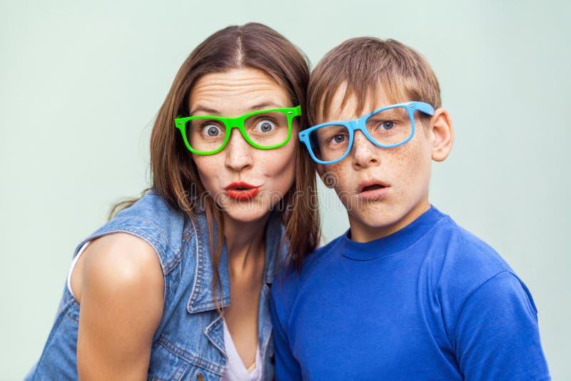 Une soeur plus âgée et son frère avec des taches de rousseur, posant au-dessus du fond bleu-clair ensemble l'heure d'été, regarda photographie stock libre de droits