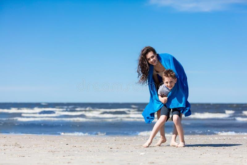 Une soeur plus âgée tenant son petit frère sur la plage images libres de droits