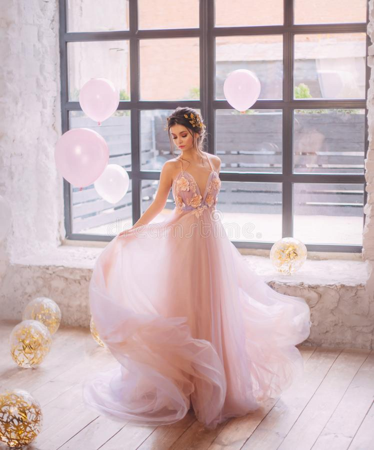 Une sorcière agréable avec une coiffure foncée et une jante magnifique danse dans la lumière, habillée dans une rose sensible ave photographie stock libre de droits