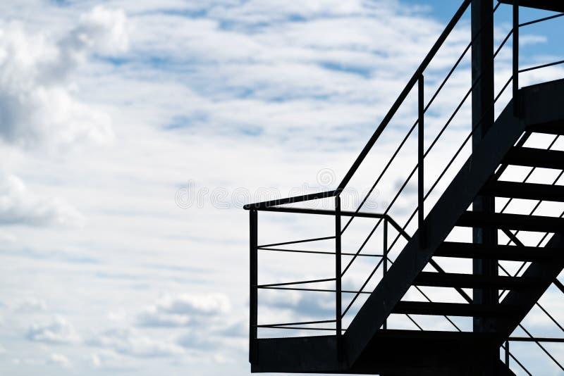 Une sortie de secours ou un escalier externe sur un bâtiment silhouetté contre un ciel nuageux image libre de droits