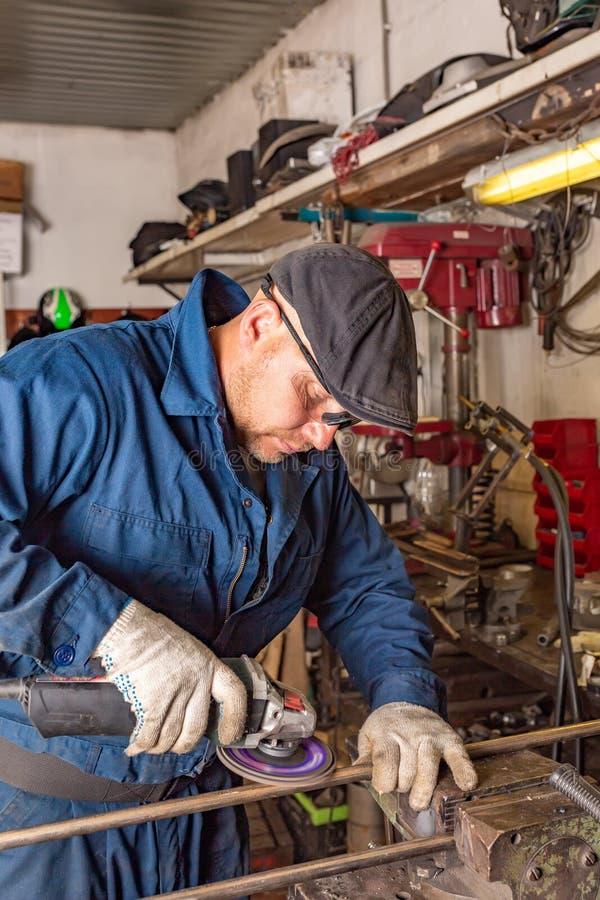 Une soudeuse de jeune homme dans un T-shirt bleu, des lunettes et des gants de construction traite le métal une broyeur d'angle d image stock