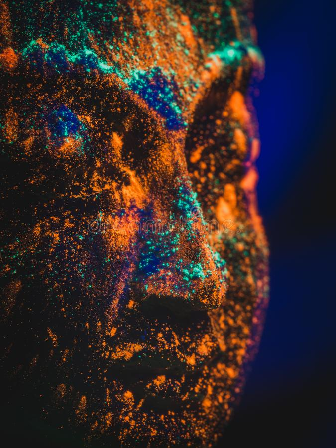 Une statue d'un dieu ou d'une divinité couverte dans la poudre UV de Holi et allumée par la lumière UV photo stock