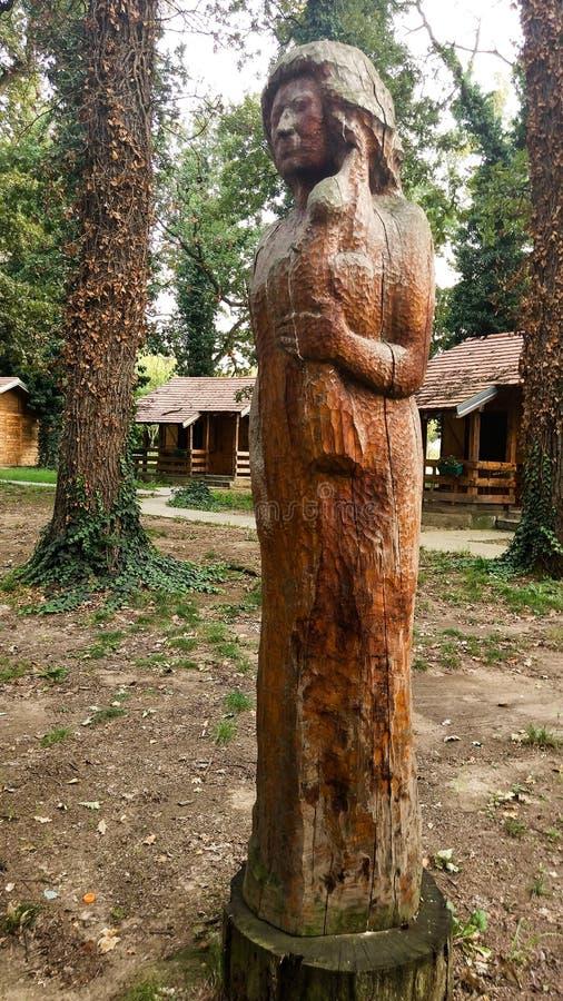 Une statue en bois d'une femme en parc, tenant un oiseau dans sa main image libre de droits
