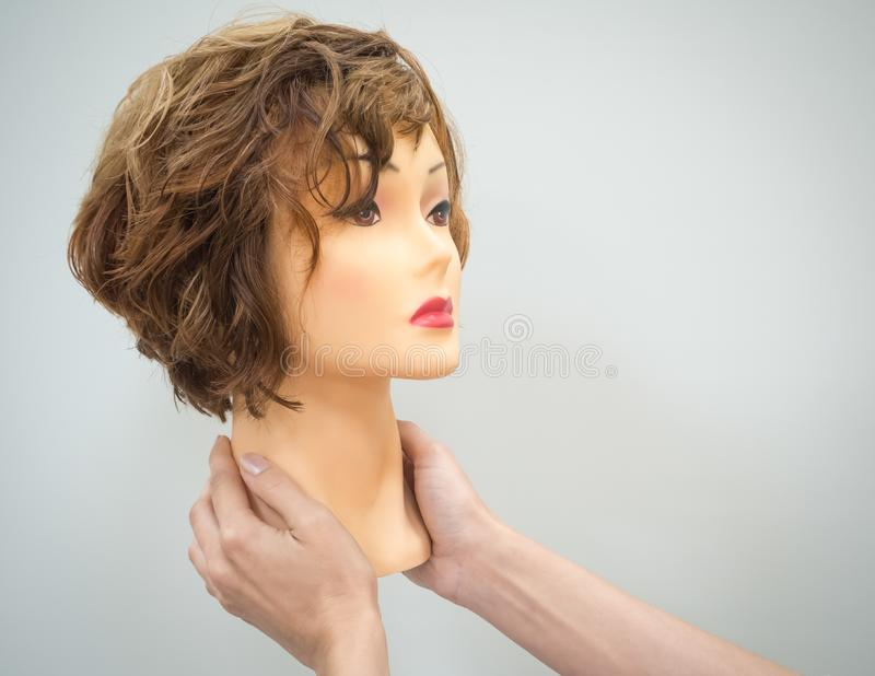 Une tête de mannequin pour la coiffure de enseignement dans des mains sur un fond clair Concept de beauté photos libres de droits