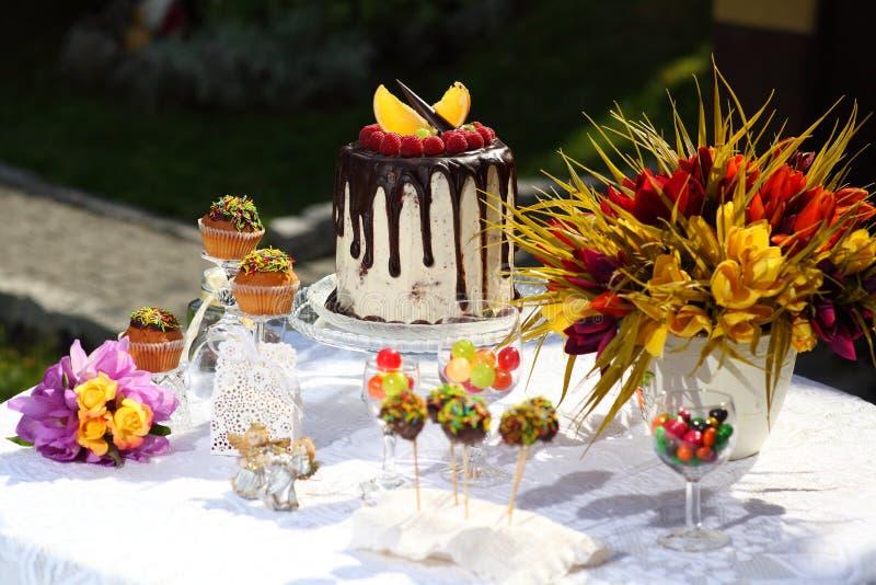 Une table de fête décorée du gâteau d'anniversaire avec des fleurs et des bonbons photos libres de droits