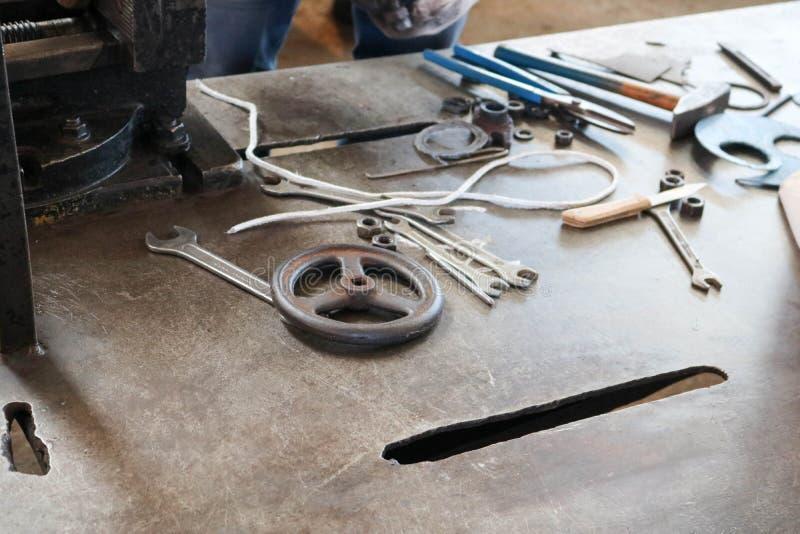 Une table de fer avec un outil de métal ouvré, clés, marteaux, tournevis, pinces, couteaux, valves dans l'usine, une usine images stock