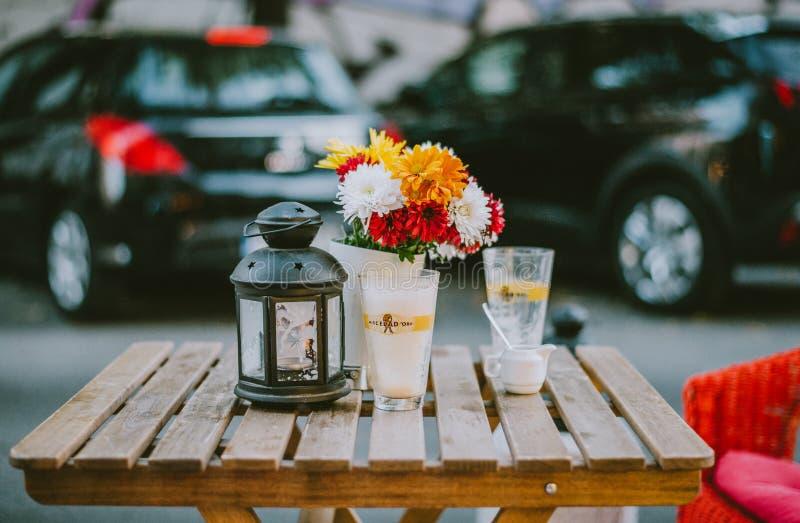 Une table de rue avec des fleurs et un verre photographie stock libre de droits