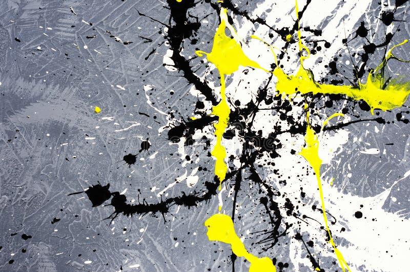 Une tache de la peinture renversée blanche et noire et jaune sur une surface texturisée concrète photos libres de droits