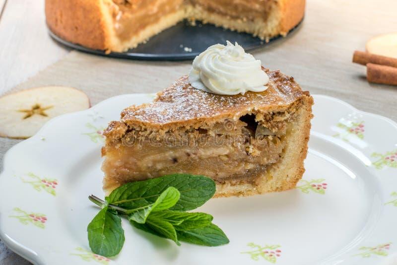 Une tarte aux pommes de tranche avec de la crème et la menthe fouettées d'un plat image libre de droits