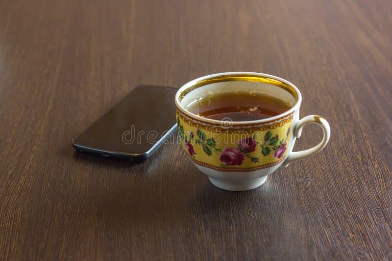 Une tasse avec un thé et téléphone portable sur le fond en bois photo stock