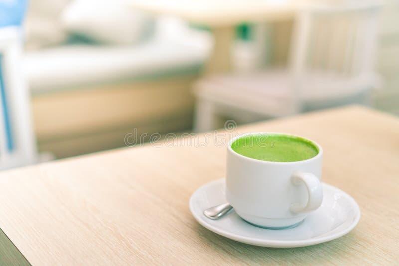 Une tasse blanche de latte de thé vert sur la table en bois dedans avec la boutique de café de café de tache floue image libre de droits