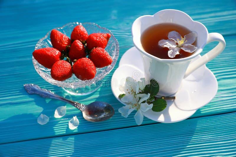 Une tasse blanche de thé avec les fleurs et la fraise de pomme image stock