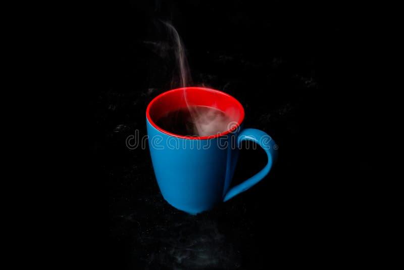Une tasse bleue de fond noir de cuisson à la vapeur chaud de café photographie stock
