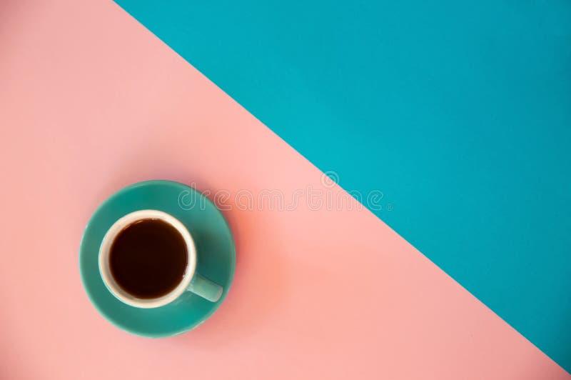Une tasse bleue de supports de café sur un rose et un fond bleu Petit d?jeuner de matin, affaires image libre de droits
