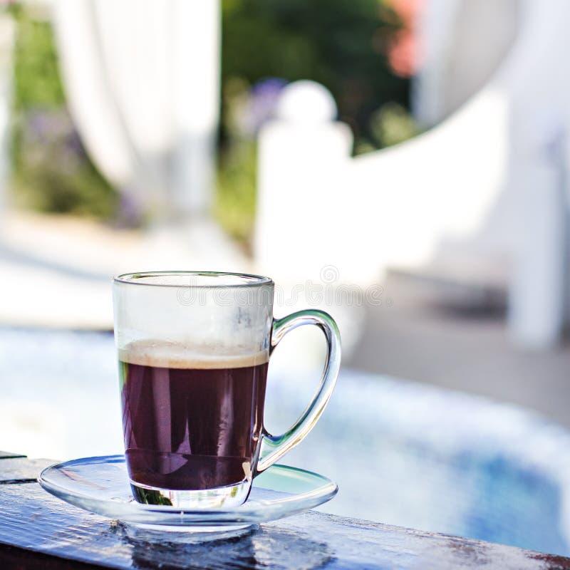 Une tasse d'expresso et une piscine à l'arrière-plan Café de matin Petit déjeuner d'été images stock