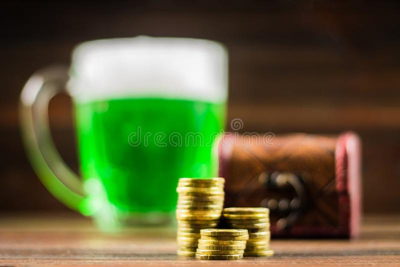 Une tasse de bière verte sur la table Lames de tréfle blanc Coffre d'or, pile de pièces de monnaie Jour de s de StPatrick ' photo libre de droits
