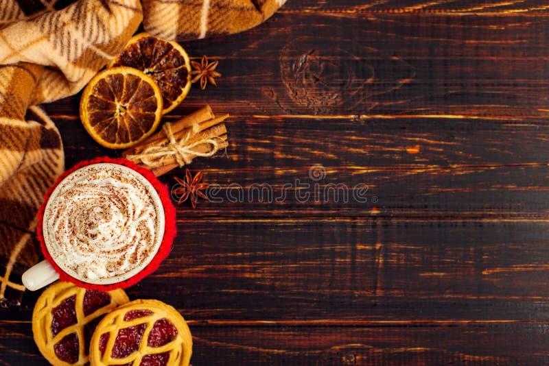 Une tasse de boisson chaude avec de la crème et la poudre fouettées, dans une couverture tricotée et des biscuits faits maison, C photographie stock