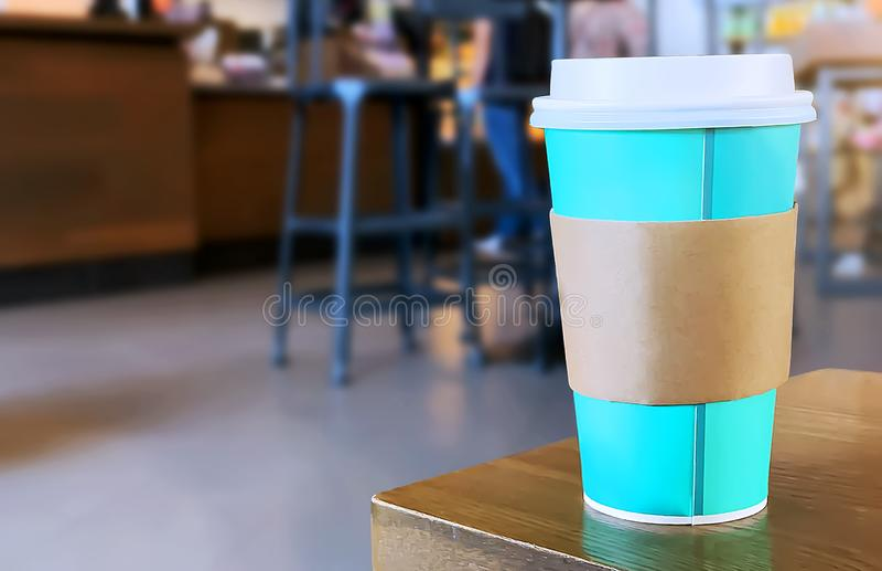Une tasse de café à emporter avec le fond brouillé du café image libre de droits