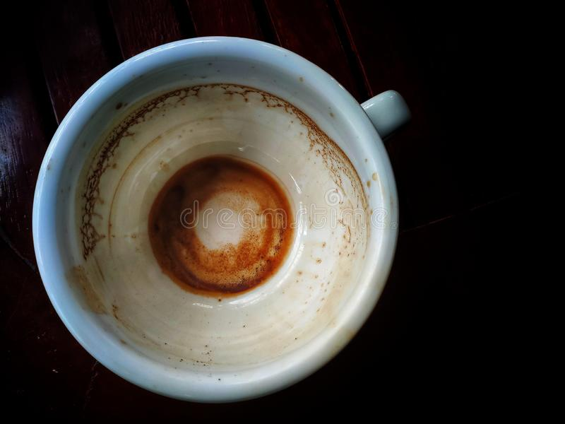Une tasse de café après avoir bu et vu seulement les chutes de café sur le fond image libre de droits