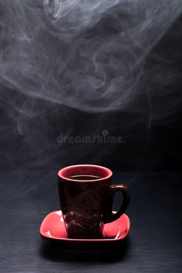 Une tasse de café avec de la fumée sur le fond noir photos stock