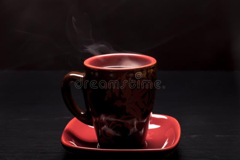 Une tasse de café avec de la fumée sur le fond noir image stock