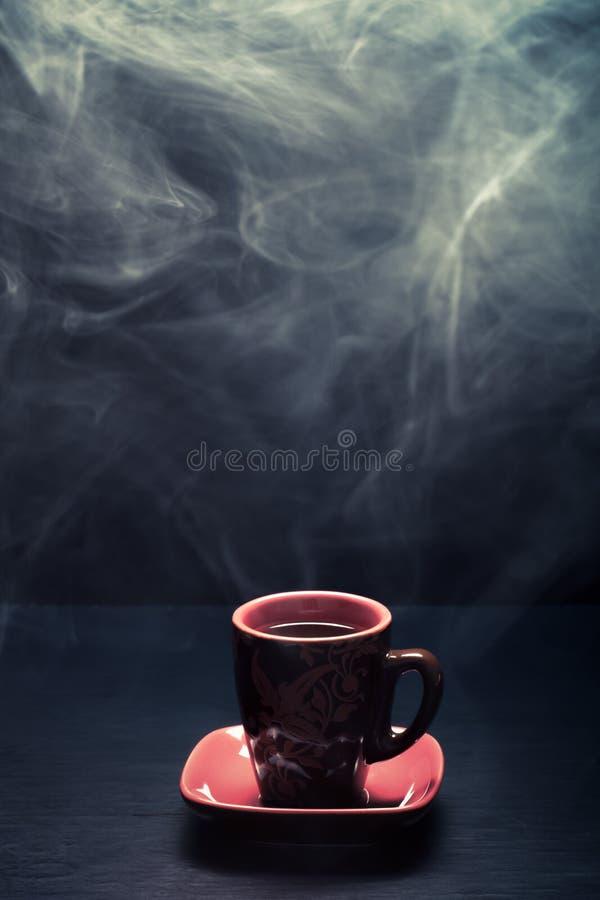 Une tasse de café avec de la fumée sur le fond noir toned photographie stock