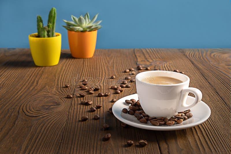 Une tasse de café avec des grains de café sur une table en bois avec les pots de fleurs colorés, foyer sélectif photos libres de droits