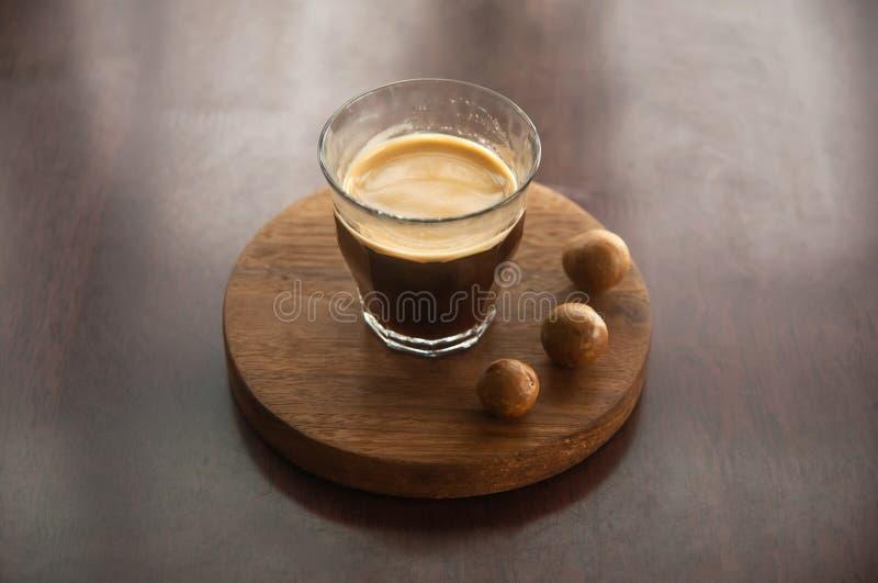 Une tasse de café avec la macadamia sur le plateau en bois rond sur le bureau en bois Espace de travail simple, pause-café pendan photos libres de droits