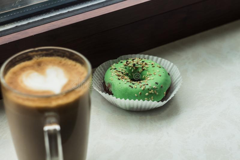 Une tasse de café avec un coeur de mousse et de beignet image libre de droits
