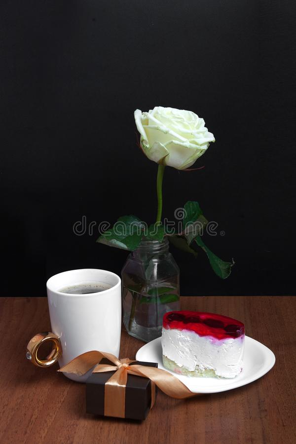 Une tasse de café avec un gâteau et une rose sur un fond noir Jour du `s de Valentine image libre de droits