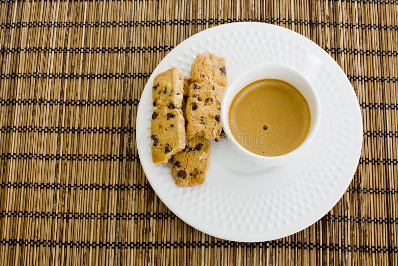 Une tasse de café blanc et de gâteaux aux pépites de chocolat au-dessus d'un t en bois images stock