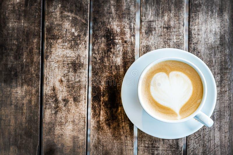 Une tasse de café de cappuccino avec un coeur peint se tient sur une table texturisée en bois Vue sup?rieure, plan rapproch? L'es photographie stock