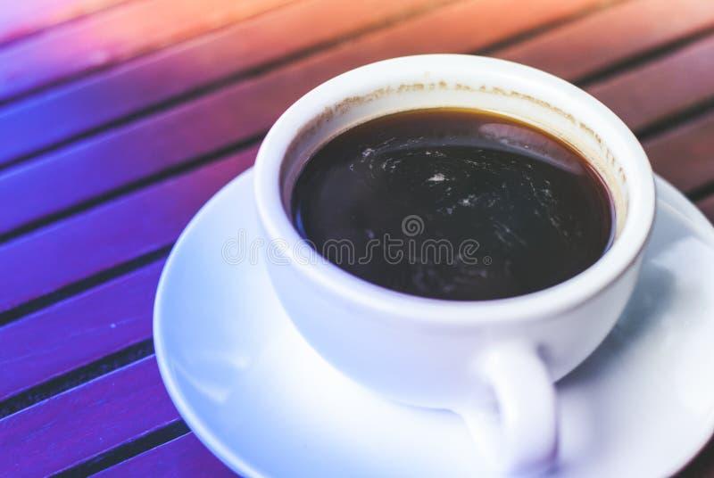 Une tasse de café chaud d'expresso de plat sur la table en bois dans le temps de précipitation de matin photos stock