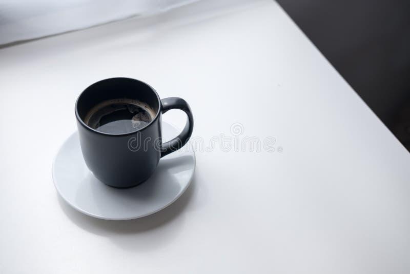 Une tasse de café chaude noire avec la soucoupe blanche sur le fond en bois de table et de rideau de vintage en café de minimalis photographie stock libre de droits