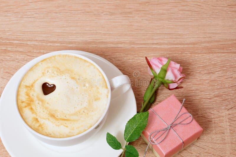 Une tasse de café, d'une boîte avec un cadeau et d'une s'est levée Table en bois image stock