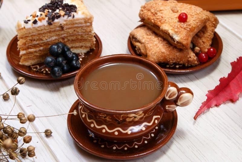 Une tasse de café, des biscuits de fruit, du gâteau et d'un chiffre d'un chat rouge sur la table Fond blanc Usine de lin sèche Pl photos libres de droits