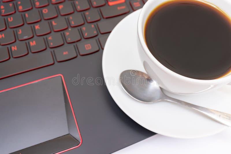 Une tasse de café en céramique blanche sur l'ordinateur portable pendant le matin photo stock