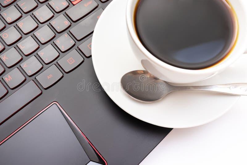 Une tasse de café en céramique blanche sur l'ordinateur portable pendant le matin photos libres de droits