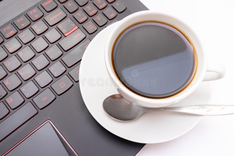 Une tasse de café en céramique blanche sur l'ordinateur portable pendant le matin photographie stock libre de droits