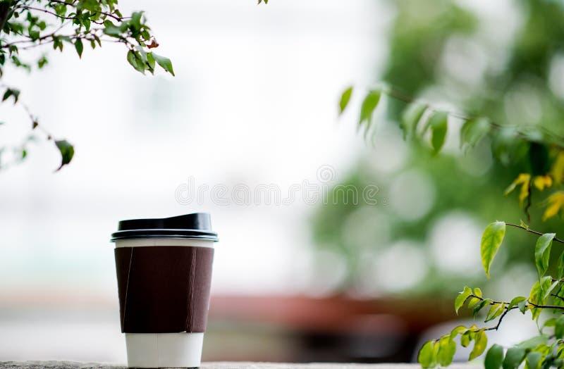 Une tasse de café est placée dans les mains et dans le plancher avec un n photographie stock