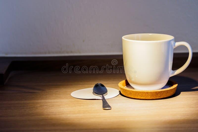Une tasse de café est placée sur un plancher en bois images stock
