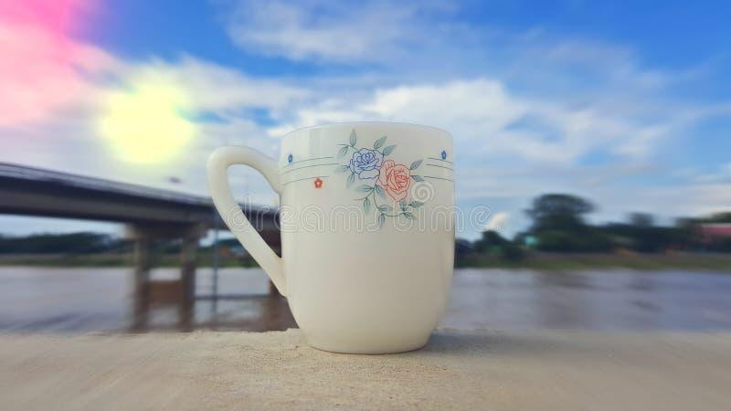 Une tasse de café est placée sur un plancher en bois photos libres de droits