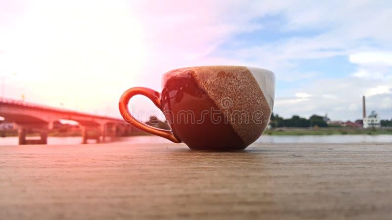Une tasse de café est placée sur un plancher en bois pendant le matin image libre de droits