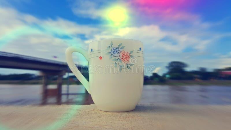 Une tasse de café est placée sur un plancher en bois pendant le matin images stock
