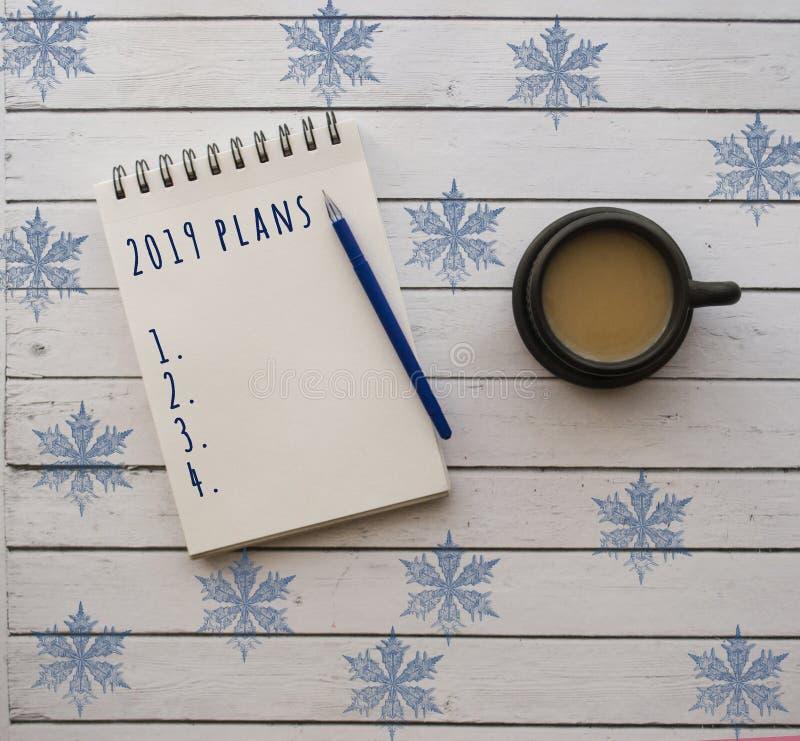 Une tasse de café et de bloc-notes sur la table en bois blanche photographie stock libre de droits