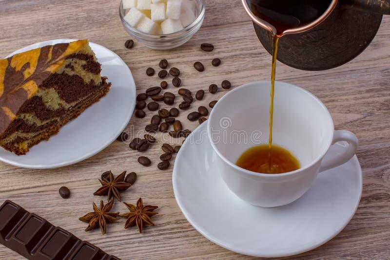 Une tasse de café et d'un gâteau savoureux sur une soucoupe Barre de chocolat, grains de café, une cuvette avec des cubes en sucr photographie stock libre de droits