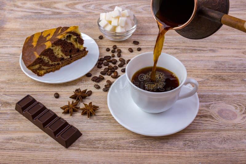 Une tasse de café et d'un gâteau savoureux sur une soucoupe Barre de chocolat, grains de café, une cuvette avec des cubes en sucr images libres de droits