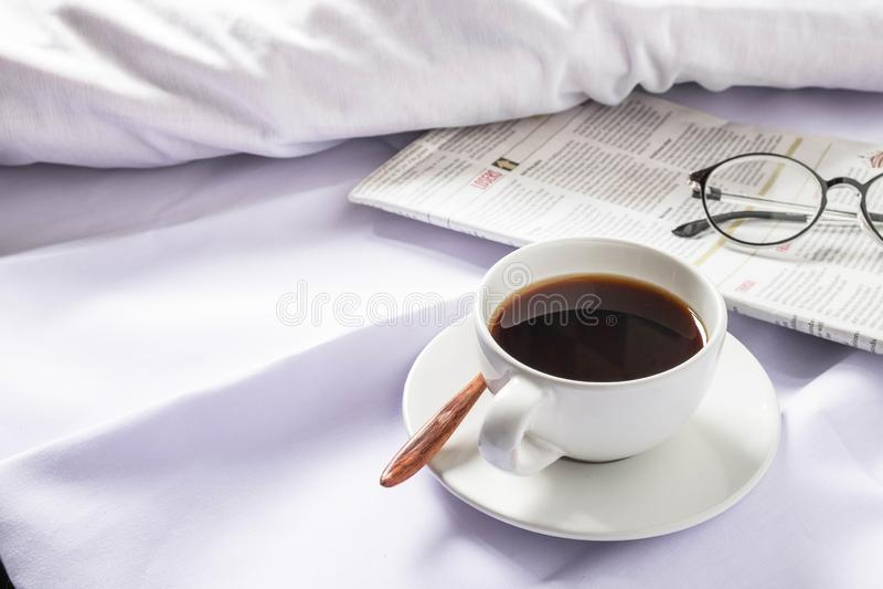 Une tasse de café et d'un journal sur un lit blanc pendant le matin photo stock