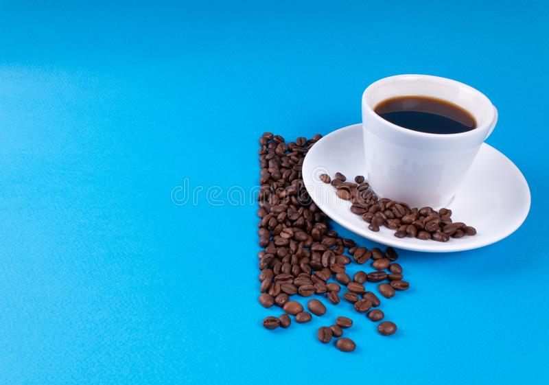 Une tasse de café noir avec des grains près de elle sur un fond bleu image stock